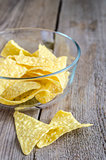Heap of corn chips in the glass bowl on the wooden background