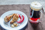 Grilled chicken drumsticks with a mug of beer