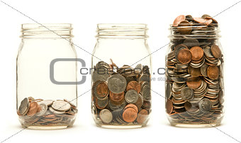 Three glass jars holding coins