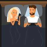 Happy couple using digital devices in bed at night.