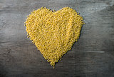 millet grains formed in heart shape on wooden background
