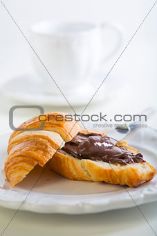 Breakfast with croissant and chocolate.