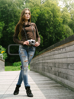 Beautiful woman outdoors with vintage camera