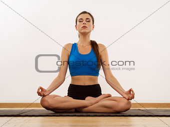 Young woman doing yoga lotus position