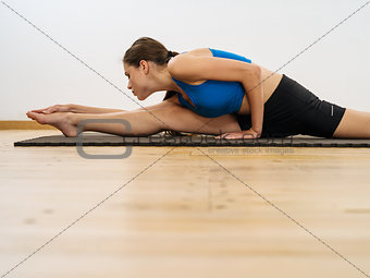 Woman stretching her legs in the gym