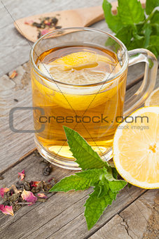 Green tea with lemon and mint on wooden table