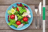 Fresh healthy salad, tomatoes and kitchen utensils
