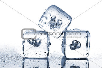 Three melting ice cubes with water dew