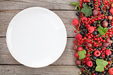 Fresh ripe berries and empty plate on wooden table