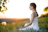 Young Beautiful Woman Practices Yoga on the Sunny Meadow