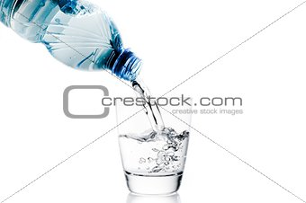 pouring a glass with water trough little blue bottle