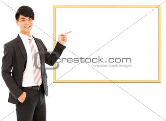 asian smiling businessman pointing blank board