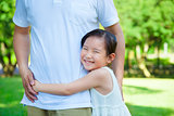 smiling little girl hug father waist in the park