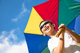 happy little boy hold a colorful umbrella with blue sky