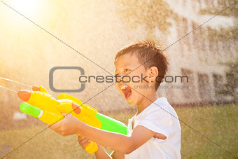 little boy shouting and playing water guns in the park