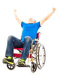 excited young man sitting on a wheelchair and raising hands