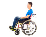 hopeful young man sitting on a wheelchair in studio