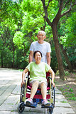senior woman sitting on a wheelchair with his husband