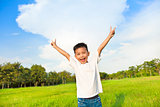 happy children standing on meadow and raise hands