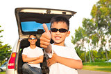 cool boy thumb up and father across arms with car