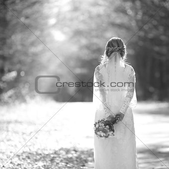 Caucasian beautiful bride spinning around with veil in hand.
