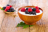 Yogurt with wild berries in wooden bowl