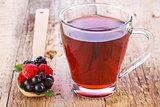 Fruit red tea with wild berries in wooden spoon