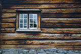Dark country timbered wooden loghouse wall with window