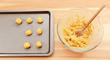 Adding balls of cookie dough to a baking sheet