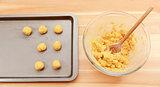 Adding balls of cookie dough to a baking sheet