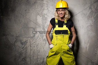 Attractive builder woman posing against grunge wall
