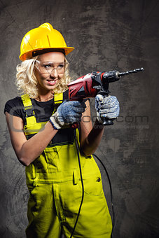 Attractive builder woman with a drill in her hands