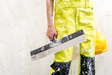 Construction worker with putty knife over obsolete background