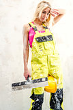 Tired female construction worker with putty knife working indoor
