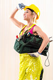 Female construction worker with tool bag indoors
