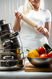 Raw vegetables and woman holding rolling-pin on background