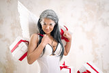 Young woman as angel with heap of gift boxes posing indoors