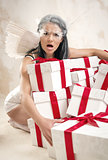 Young woman as angel with heap of gift boxes