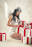 Beautiful young woman as angel with heap of gift boxes