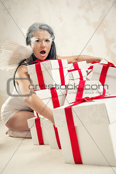 Beautiful young woman as angel with heap of gift boxes indoors