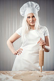 Woman holding rolling pin wearing uniform posing indoors