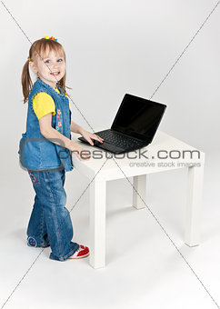 little girl in blue jeans standing at a table with a laptop