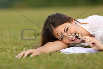 Candid happy woman lying on the grass writing