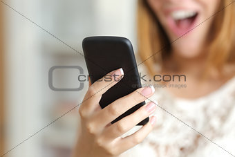 Close up of a surprised woman using a smart phone at home