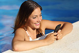 Happy girl using a smart phone in a swimming pool in summer vacations