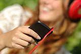 Woman hand using a smart phone to listen to the music with headphones