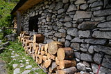 Side of old cottage with wood pile