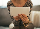 Closeup on young woman sitting on couch and using tablet pc