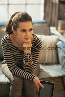 Thoughtful young woman with tablet pc sitting on couch