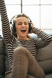 Portrait of happy young woman listening music in headphones